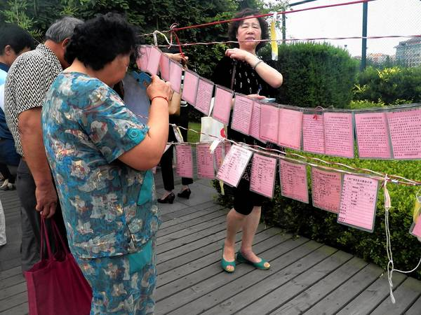 Parents look at advertisements hanging in a park in Qingdao, China, for young single men and women.