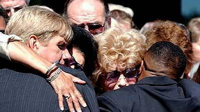 David McCourt, left, husband of Ruth McCourt and father of Juliana, and Paula Scott, second from right, Ruth's mother, embrace friends in East Lyme, Conn.