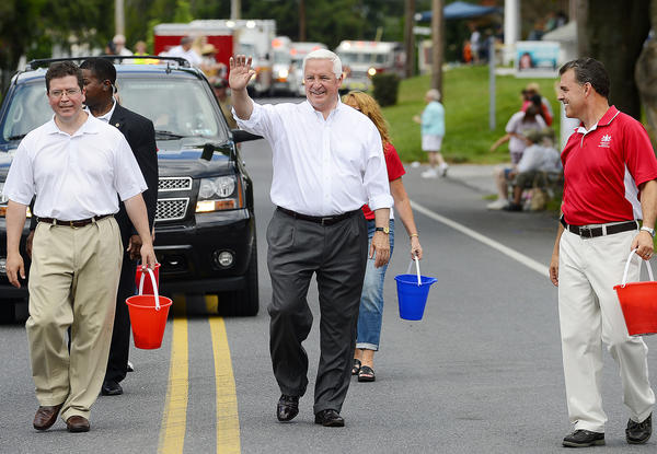 Pennsylvania Gov. Tom Corbett, center, waves to those watching the parade Saturday afternoon during the Mont Alto Centennial Parade.