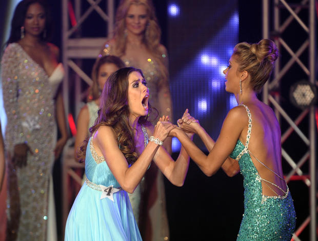 Miss Fort Lauderdale USA's Brittany Oldehoff, center, reacts to being named Miss Florida USA 2014 during their pageant Saturday, July 13, 2013, at Broward College's Bailey Hall Auditorium.  Miss Wellington USA Briegitte Baldrica, right, was named first runner-up.