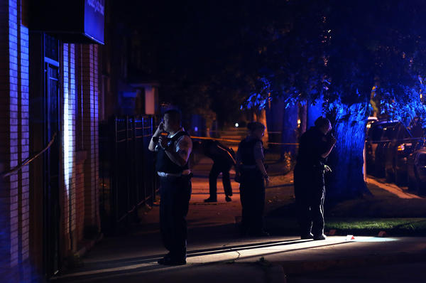 Police investigate the scene where a 19 year-old woman was shot in the Austin neighborhood on July 14.
