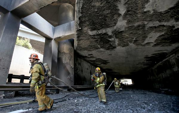Firefighters inspect a freeway tunnel after a tanker truck overturned and caught fire.