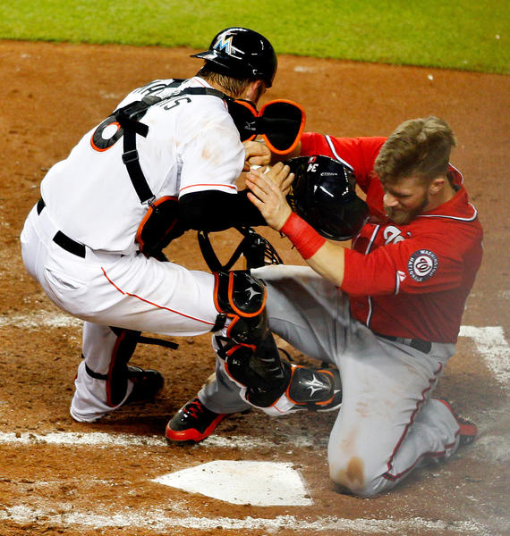 Jul 13, 2013; Miami, FL, USA; Washington Nationals left fielder Bryce Harper (34) collides with Miami Marlins catcher Jeff Mathis (6) and is safe at home plate in the fourth inning at Marlins Park. Mandatory Credit: Robert Mayer-USA TODAY Sports ORG XMIT: USATSI-123128