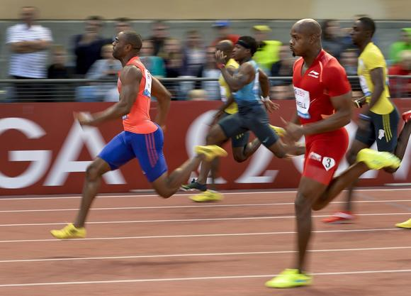 Tyson Gay (L, orange shirt) besting Jamaica's Asafa Powell (red) at the Diamond League meet July 4 in Lausanne, Switzerland.  Both confirmed Sunday they have tested positive for banned substances. (Fabrice Coffrini/ AFP / Getty Images)