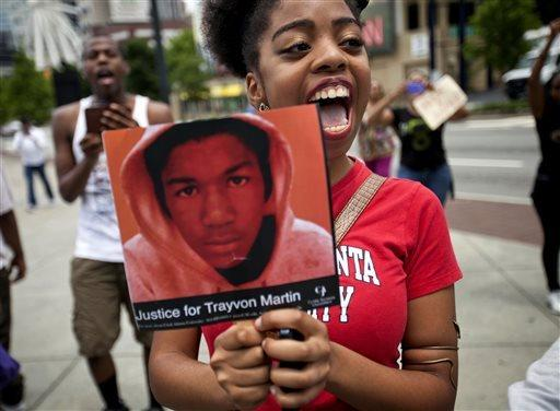 Averri Liggins, 22, of Atlanta holds a photo of Trayvon Martin during a protest the day after George Zimmerman was acquitted of Martin's 2012 slaying.