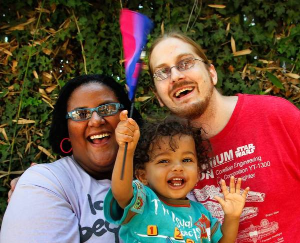 "Faith Cheltenham's 1-year-old son Storm waves a flag honoring bisexuals before heading to a Fourth of July gathering with her husband, Matt Kanninen. Faith is a bisexual activist and is vocal about the ""B"" being ignored in the LGBT community."