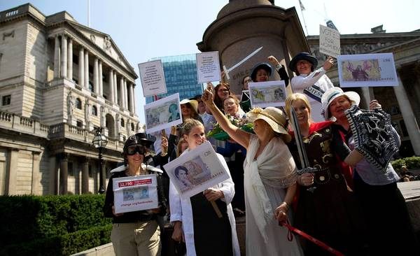 In London, campaigners dressed as famous women from history deliver to the Bank of England a petition calling for female representation on bank notes.