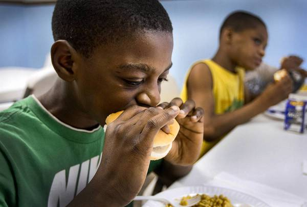 Rakeese Timmons, 10, left, and his brother, Rakeem, also 10, dig into their lunches during summer school students at the East End Academy.
