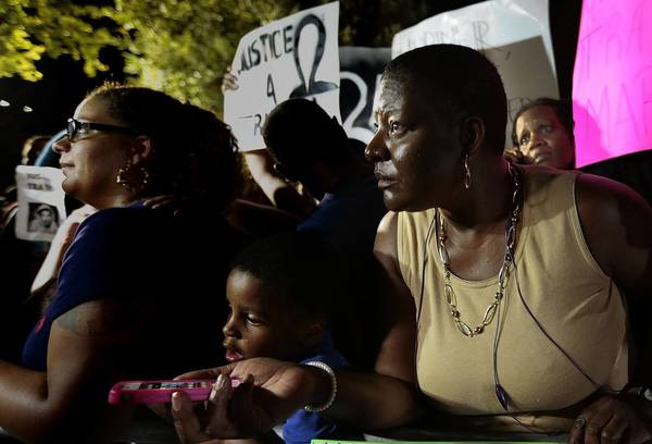 Supporters of Trayvon Martin's family listen Saturday night over their smartphones as the verdict is read in the George Zimmerman trial.