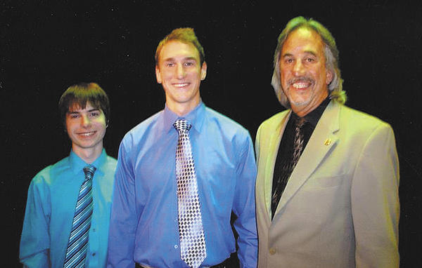 Williamsport Rotary Club member Brent Bailey, right, presents sholarships to two Williamsport High School seniors, from left, Connor X. McNaney and Benjamin M. Seibert.