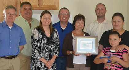 From left are Mark Lauseng, executive director of the South Dakota Housing Development Authority; Harley Overseth, real estate broker associate; Roxanne Woodring, USDA housing specialist; Jeff Mitchell, Homes Are Possible Inc. executive director; Elsie Meeks, USDA Rural Development state director; Wade Veflin, housing loan coordinator for Grow SD; and homeowner Kelly Martin and her daughter, Jordan. Martin became a first-time homeowner by working with USDA Rural Development to obtain a 502 Direct Single Family Housing Loan to purchase the two-bedroom residence in Mobridge.