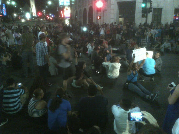 Protesters angered by the acquittal of George Zimmerman in the death of unarmed teenager Trayvon Martin sit in the intersection of Hollywood Boulevard and Highland Avenue on Sunday night.