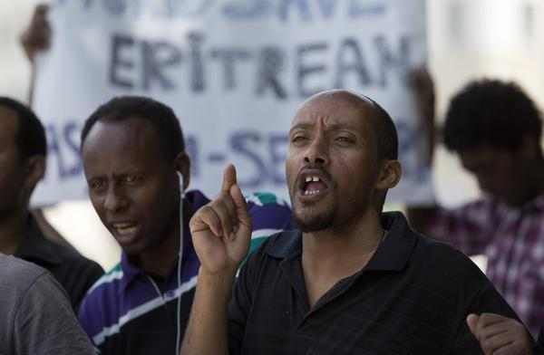 During a protest outside the prime minister's office in Jerusalem, an Eritrean immigrant calls for granting refugee status to African immigrants who made their way into Israel.