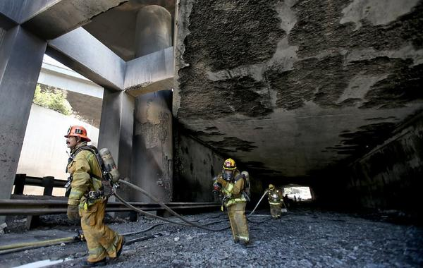 Los Angeles Fire Department firefighters pull hoses out of a freeway tunnel in Los Feliz after a big rig truck and trailer flipped and burned at the transition between the 2 and 5 Freeways on Saturday, July 12, 2013.