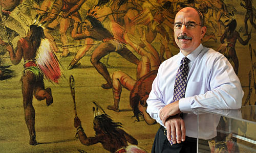 Steve Stenersen, president and CEO of U.S. Lacrosse, at their national headquarters and museum adjacent to the Johns Hopkins University campus. Behind him is a mural of an enlarged George Catlin painting showing Native Americans playing lacrosse in their museum.