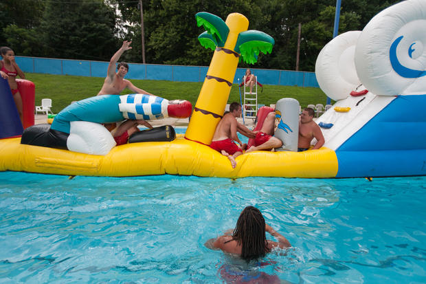Lifeguards and others traverse the slippery inflatable island and slide at the laurel municipal for Laurel municipal swimming pool