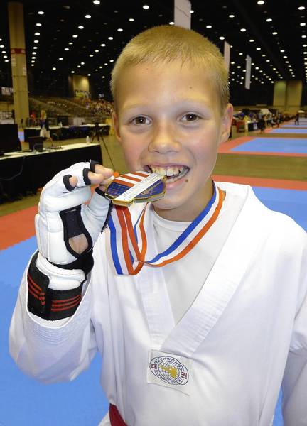 Jack Arne takes a chomp out of the gold medal he won on July 4 for winning the 10-11 age group at the USA Taekwondo Nationals in Chicago.