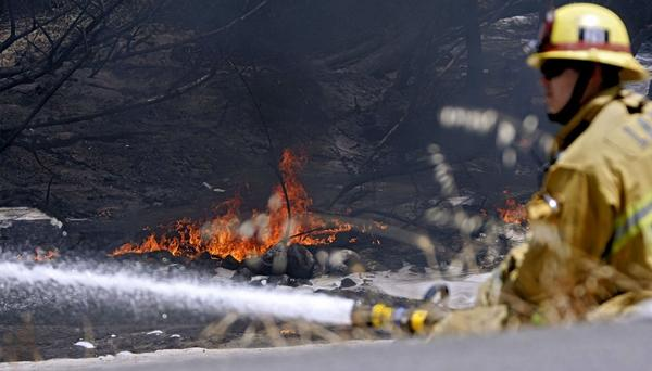 L.A. City Fire Dept. firefighter Mike Henderson from Station 60 puts water on the L.A. River as gasoline burns on top of the water in Los Angeles south of Glendale on Saturday, July 13, 2013. A gasoline tanker flipped over and caught fire at the nearby 2 Freeway transition to the 5 Freeway and spilled some of the 7,000 gallons of gasoline it was carrying.
