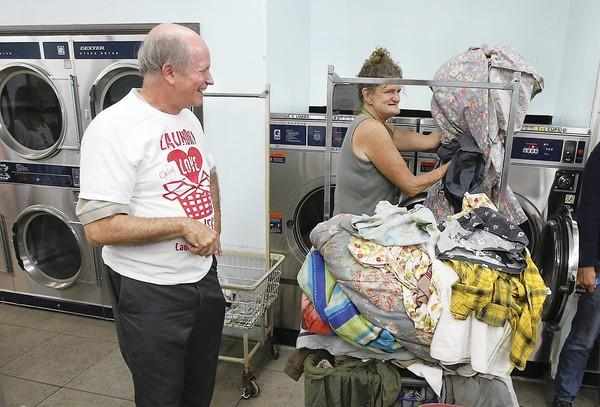 Colin Stewart laughs with a woman he helped during Laundry Love HB, which helps homeless people and those in need wash their clothes.