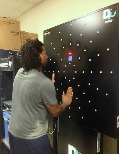 Old Dominion football player Nate Barnes uses the Dynavision machine, which is part of athletes' hand-eye coordination training.