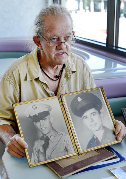Lee Blevins of Hagerstown holds two black-and-white portraits of his late brothers, Lonnie Gene Blevins, left and Heren Kline Blevins, at right. The remains of Heren Blevins were found in the area of the Death Valley POW camp and turned over to the United Nations by North Korea.