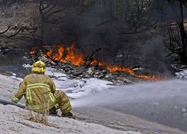 L.A. City Fire Dept. firefighter Greg Madrigal puts water on the L.A. River as gasoline burns on top of the water in Los Angeles south of Glendale.