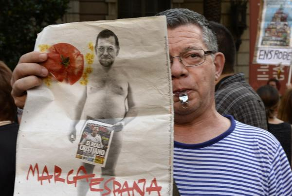 A protester holds a placard depicting Spanish Prime Minister Mariano Rajoy during a demonstration against corruption outside the Popular Party's headquarters in Barcelona.
