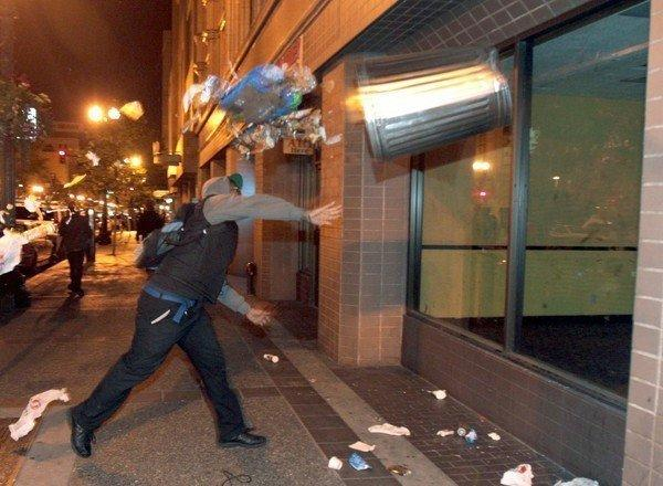 A man throws a trash can at the window of a building during a protest in Oakland early Sunday after George Zimmerman was found not guilty in the shooting death of Trayvon Martin.