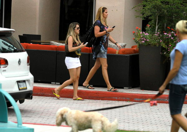 fl-boca-mizner-outdoor-dining15b---Two people walk around an outdoor couch for Max's Grille customers in Mizner Park. The outdoor dining is so popular, it's encroaching on city-owned property. And that presents a liability concern that the city is trying to work out with GGP. Carline Jean, Sun Sentinel