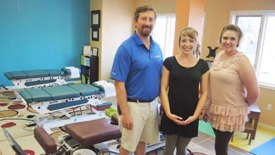 Chiropractor Kyle Denholm (from left), front desk coordinator Jeanine Endsley and office manager Kendra Denholm stand in the open-bay adjustment area at Breath of Life Chiropractic Wellness Centers new Petoskey location. Denholm said having several chiropractic tables in a common area can improve efficiency and encourage interaction among patients.