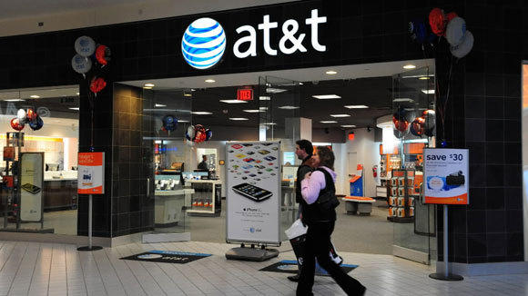 Shoppers pass an AT&T phone store at the Mall of America in Bloomington, Minn., in a 2009 file photo.
