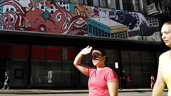 "A pedestrian shades her eyes from the morning sun as she passes ""Float,"" a mural by Noah MacMillan on South State Street."