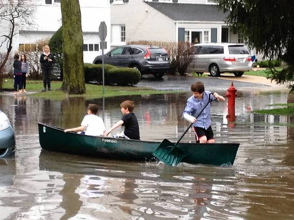 In a photo provided by Wilmette resident Renee Sexton, children play in the flooded streets of the Kenilworth Garden neighborhood after the mid-April storm.