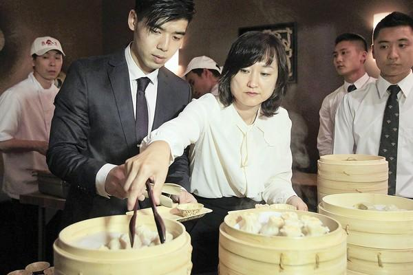 Co-owner Joanne Yang, center right, and Assistant Manager Kevin Hsiung, center left, hand out dumplings during a preview for Din Tai Fung at South Coast Plaza on Monday. The restaurant, set to open in the spring of 2014, will take over the space where McDonald's was in the Sears wing.