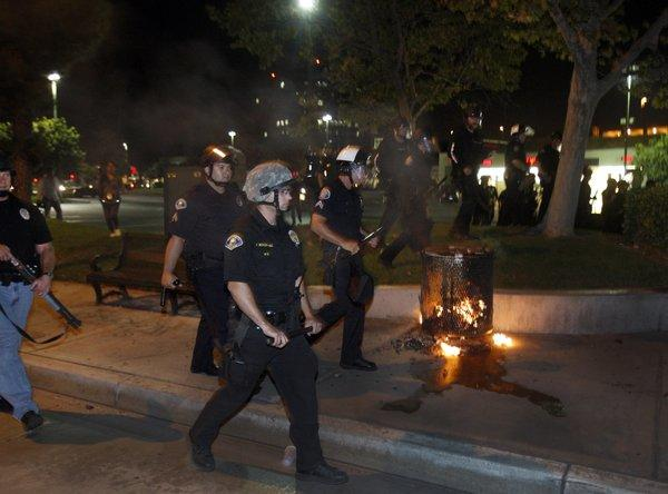 Anaheim police dressed in riot gear pass by burning trash during violent protests last summer.