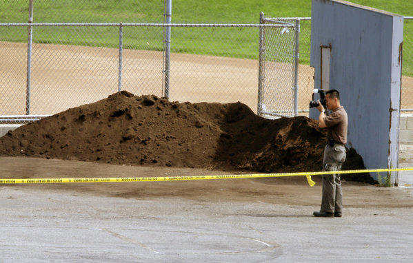 An investigator takes pictures near an athletic field in Manhattan Beach where the body was found last week.