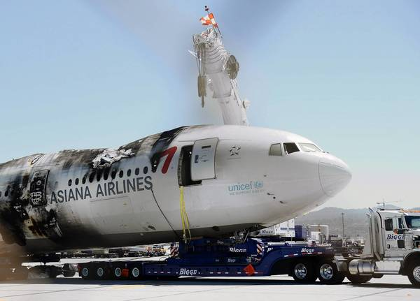 The wreckage of Asiana Airlines Flight 214 is moved from a runway at San Francisco International Airport.