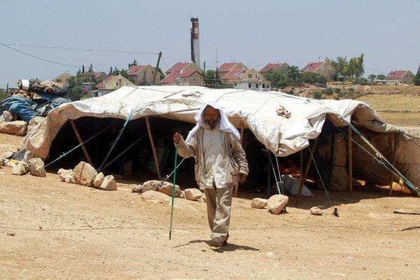 A Palestinian man walks outside his family's home, which consists of tents and shacks, near the Jewish settlement of Karmel in the West Bank.