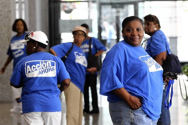 People wearing T-shirts for the activist group Action Now enter the Dirksen U.S. Courthouse on Tuesday to watch testimony in two lawsuits that aim to block Chicago Public Schools from closing 49 elementary schools and one high school program.