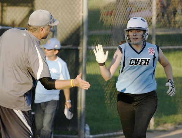 Crescenta Valley-Foothill's Sophie Georges, right, high fives her coach Will Thayer after hitting a two-run homer in a 12-1 win over West Lancaster.