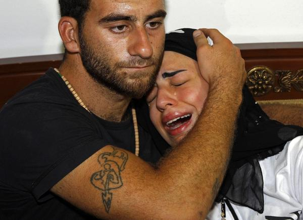 Fatima, the daughter of slain Syrian political analyst Mohammad Darrar Jammo, grieves in the comfort of a relative.