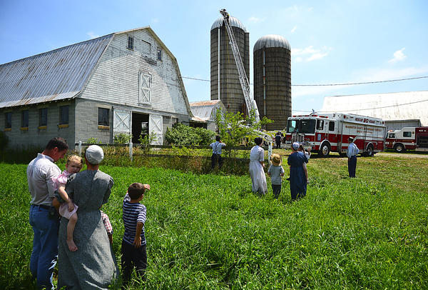 Concerned neighbors watch as rescue personnel maneuver to rescue a man injured inside a silo on a Lehmans Mill Road farm Tuesday.