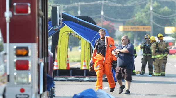 A firefighter in a hazmat suit walks up Route 17 Wednesday morning after working the scene of a chemical spill at a business in Gloucester.