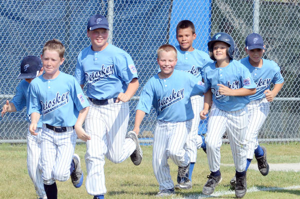 Petoskey Minor Division (ages 9-10) tournament teams Ian Piehl (second from right) is congratulated by teammates following his three-run home run in the fourth inning of Tuesdays District 13 semifinal game in Cheboygan. Petoskey defeated Cheboygan, 14-10, and will play in the District 13 championship game at 6 p.m. Thursday, July 18, in Cheboygan.