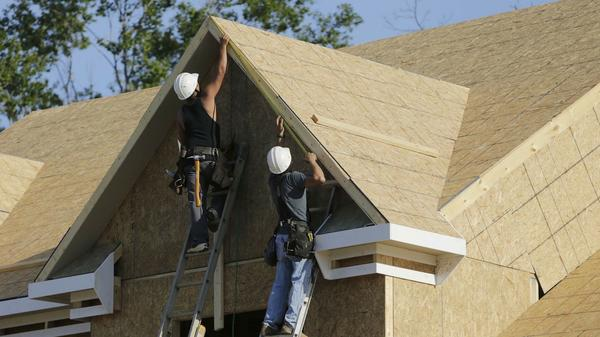 Carpenters install trim on a home in Brandywine, Md., in May.