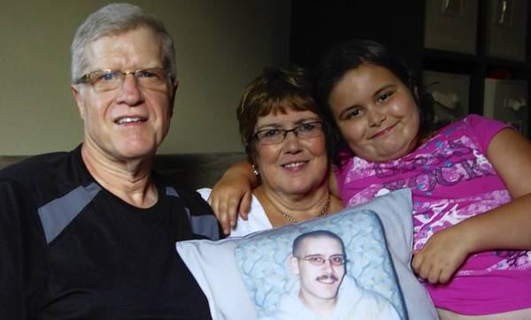 Chris Foley's family, from left, his father, Larry; mother, Vicki; and daughter, Caylee, hold a pillow with alikeness of their son and father, the namesake of Saturday's Chris Walk Night Out Against Substance Abuse.