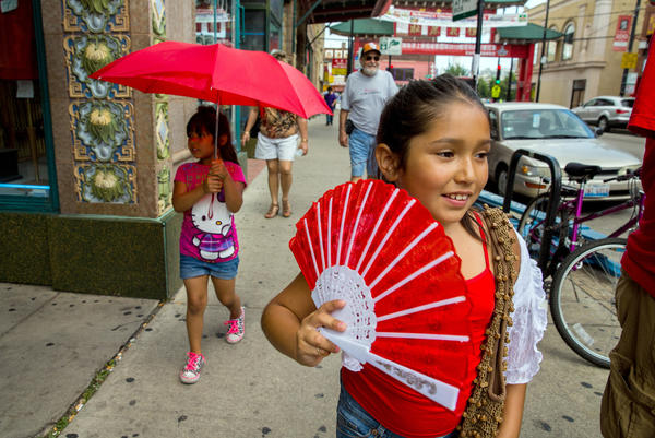 Sisters Sophie, 7, right, and Samantha Ruvalcaba, 4, use fan and umbrella to protect themselves from the heat as they walk through Chicago's Chinatown neighborhood.