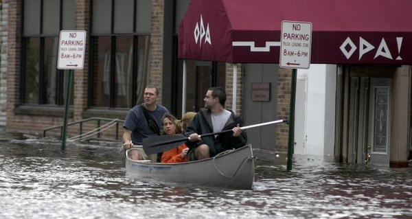 Canoeing through a flooded Fells Point after Tropical Storm Isabel in 2003. A survey finds 52 percent of Maryland households say climate change already is harming Americans.