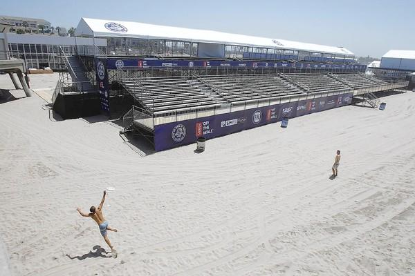 Beach-goers play frisbee in front of the main bleachers at the U.S. Open of Surfing site next to the Huntington Beach Pier.