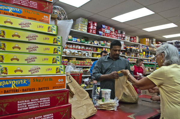 Next to a stack of dates brought in for heavy demand during Ramadan, Ada Ustjanauskas of Cosmos International gourmet grocery store checks out customer Prem Krun, left. Local grocery stores see a boom in business during the month of Ramadan.